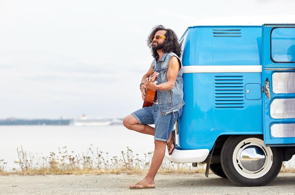 Un homme qui joue de la guitare adossé à son van