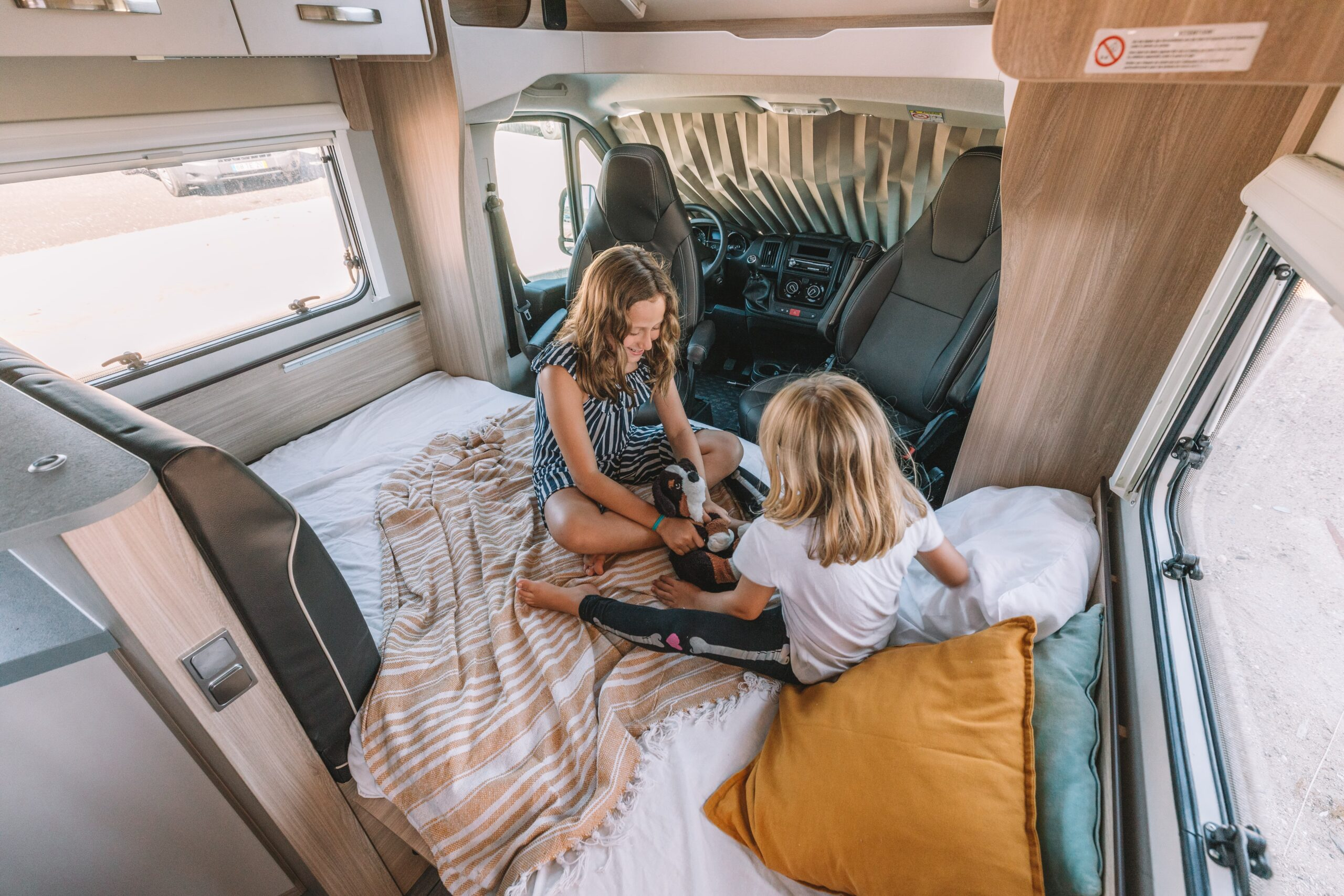 Camping with kids in an RV, two girls playing on the bed