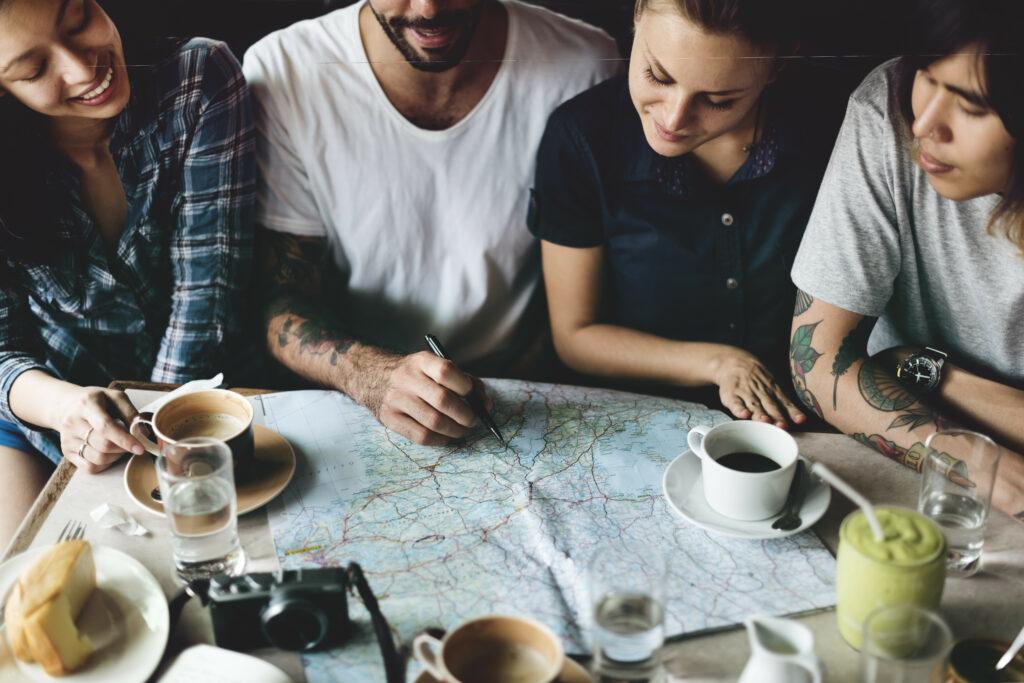 Grupo de amigos a planear um roteiro para a sua roadtrip