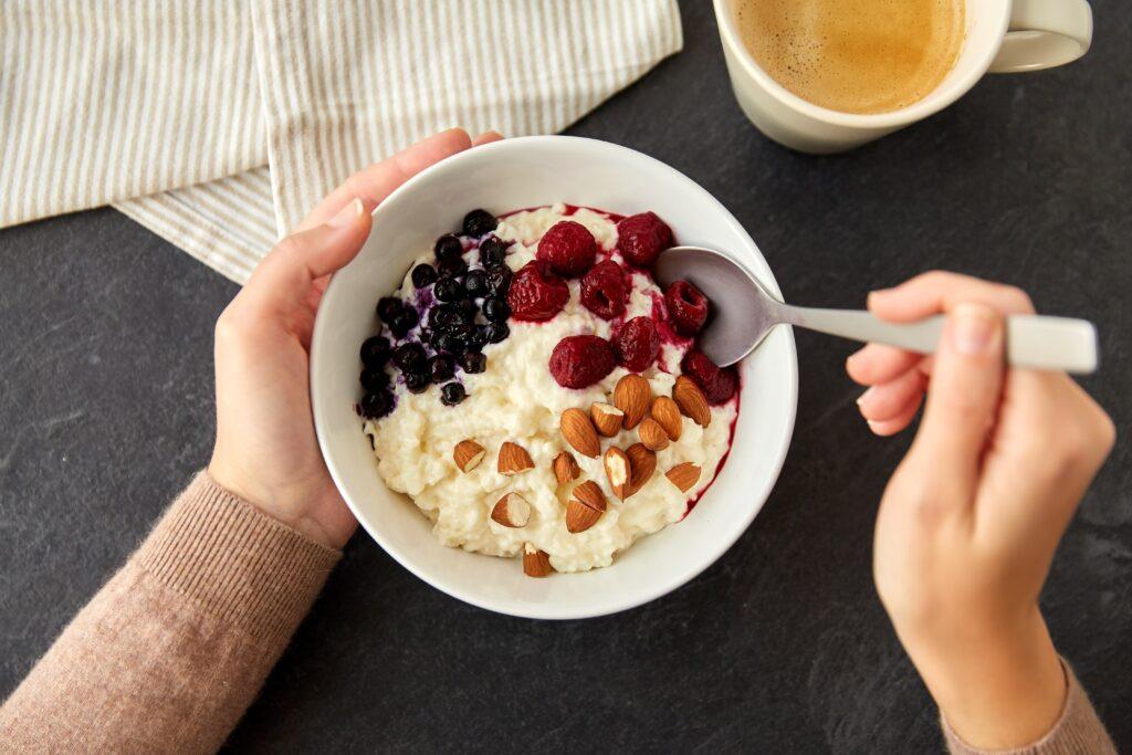 Eine Frau hält eine Frühstücksschale mit Haferbrei, Beeren und Nüssen