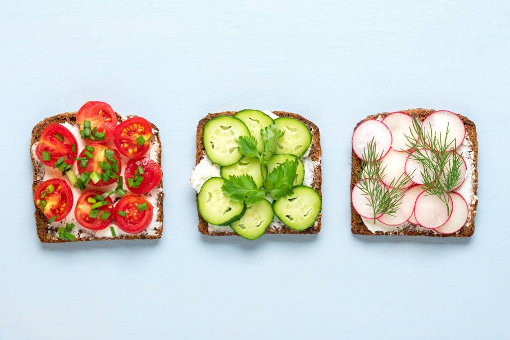Drei belegte Brote mit Tomaten, Gurken und Radieschen