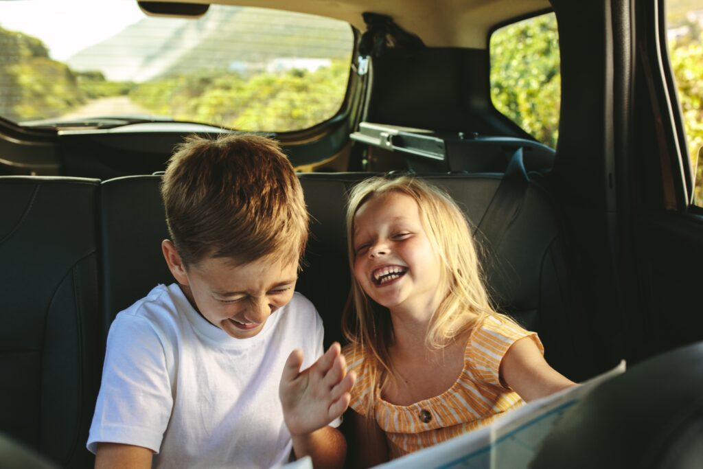 Kids having fun with road trip games in the back seat